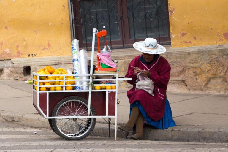 Une bolivienne en habit traditionnel, qui vend du jus de fruit dans la rue. Et si elle n'a pas de client, elle tricote ;)