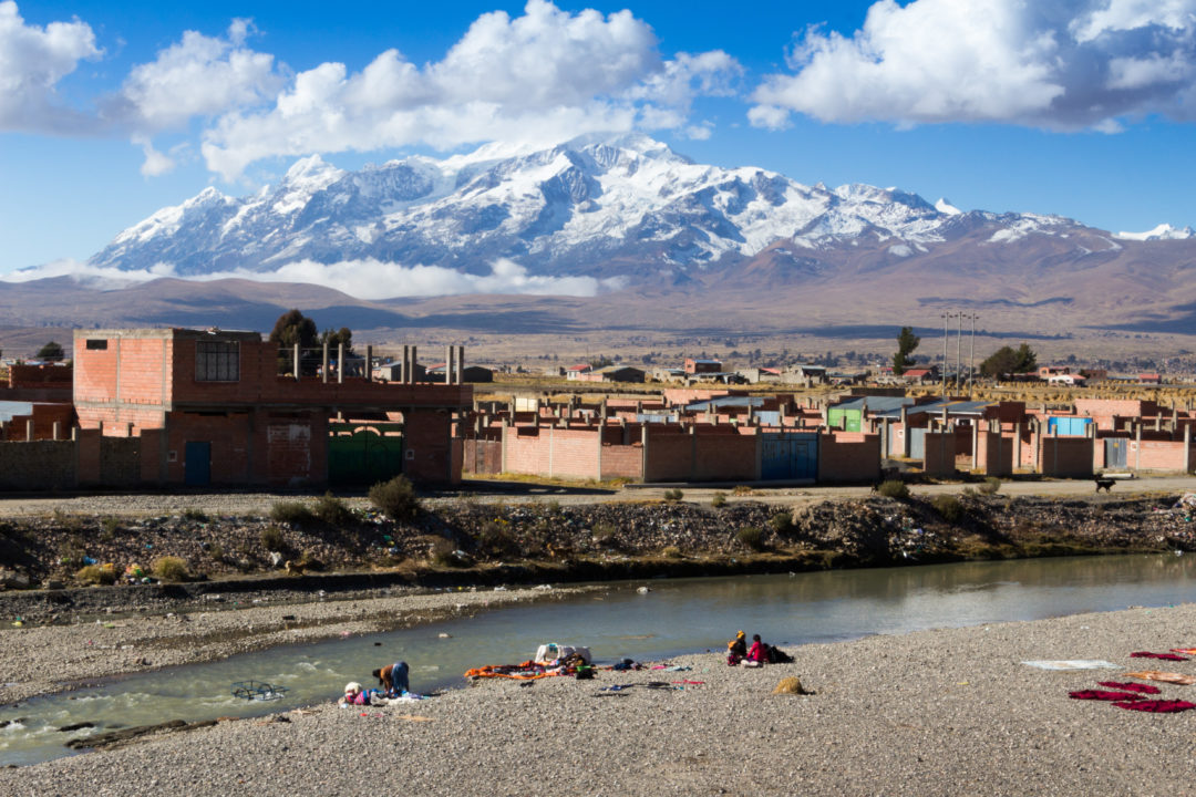 Sur la route au nord du lac Titicaca, activité lessive dans la rivière, avec le Nevado Illampu en arrière plan.